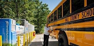 School employee fuels a propane school bus.