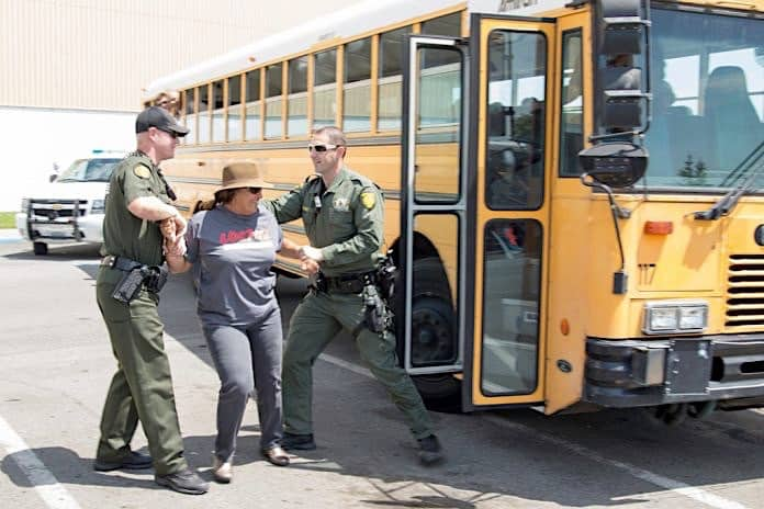 Police arrest parent trying to board school bus.