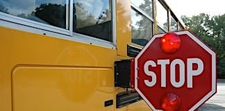 School bus with stop arm deployed and LED lights flashing.