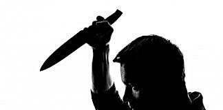 Silhouette of man wielding knife