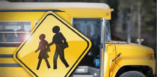 Crossing sign with school bus in background