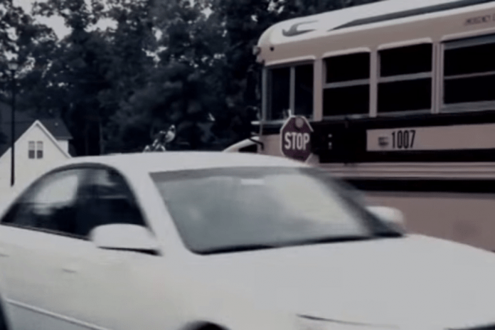 Car passing a stopped school bus