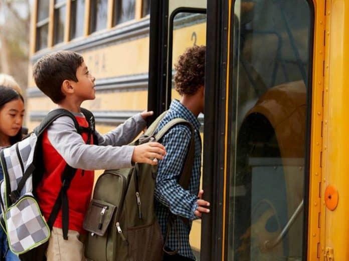 Students boarding school bus. Shutterstock photo.