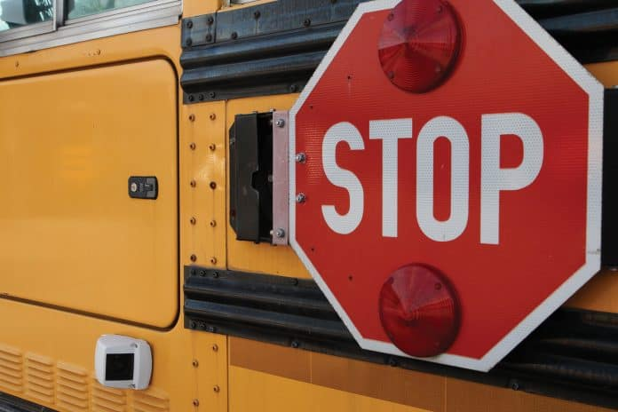 A stop arm rests flush against a school bus next to a video camera.