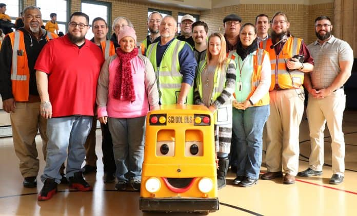 Recognized East Aurora, Illinois bus drivers pose with Buster the School Bus after a