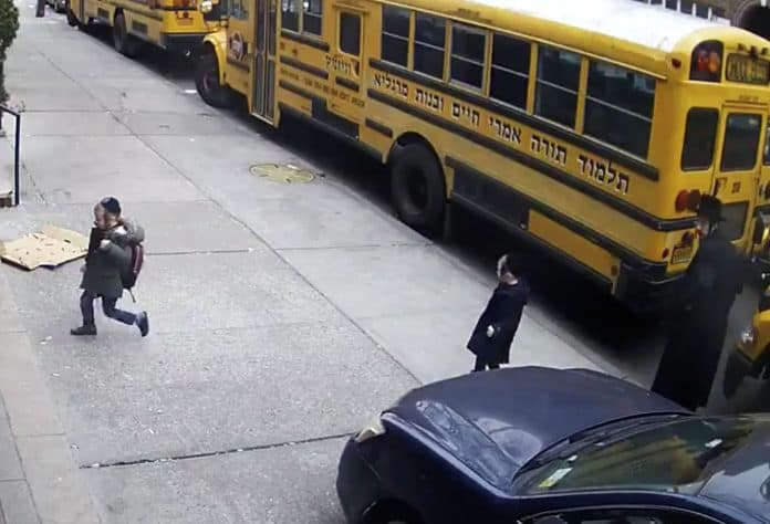 The security footage shows several young students who appear to be in preschool walking on the sidewalk after disembarking from their school bus.