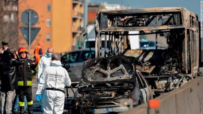 Forensic policemen and firefighters work by the wreckage of a school bus that was transporting 51 children on March 20, 2019, after it was torched by the bus' driver, in San Donato Milanese, southeast of Milan. (Photo courtesy of CNN.)