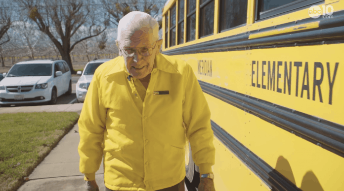 """Phil Gardner began driving a school bus when he was 20 years old; 70 years later he still loves his job. """"I used to have all my drivers in a uniform with yellow shirts and jackets. I have about 25 of those shirts in my closet, so I am wearing them every day now to wear them out.""""(Photo screenshot by ABC10.com.)"""