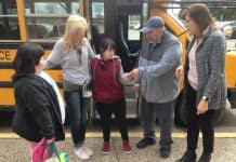 "School bus driver Gary Wozniak of Koch Bus hands a student a ""Success Ticket"" as part of a Positive Behavior and Intervention Supports program used for student transportation at Intermediate District 287 near Minneapolis. Also pictured, (left) is Laury Force, a job coach at Ann Bremeer Education Center, and (far right), Transportation Manager Amy Tiedens."