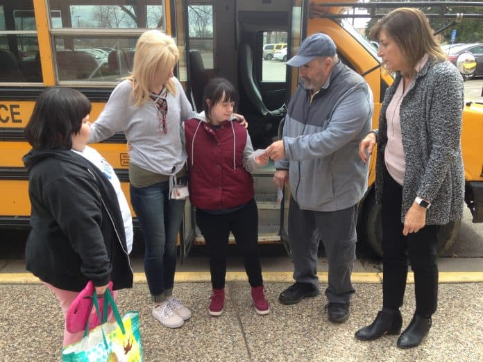 """School bus driver Gary Wozniak of Koch Bus hands a student a """"Success Ticket"""" as part of a Positive Behavior and Intervention Supports program used for student transportation at Intermediate District 287 near Minneapolis. Also pictured, (left) is Laury Force, a job coach at Ann Bremeer Education Center, and (far right), Transportation Manager Amy Tiedens."""