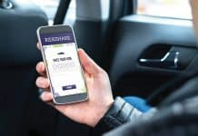 Ride share customer and passenger sitting in the backseat of a car while using the rideshare application in smartphone to give rating to the driver. Commuter and rider giving review in phone taxi app.
