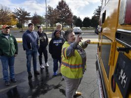 Laura Landis, a driver instructor, trainer and recruiter for Prince William County Schools in Maryland, shows teachers Kevin Loughery, Ryan Wicka, Shannon Parker, Yonika Powell, and Sharon Harrison how to perform the exterior bus inspection during a Saturday class to become bus drivers held at Parkside Middle School. (Photo courtesy of Prince William Times; photo by Randy Litzinger.)