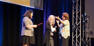 Sue Shutrump, far right, receives the 2018 Grandolfo Award from Q'STRAINT's Lisa Nippolt, center, and Linda Grandolfo.
