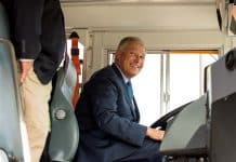 Gov. Jay Inslee sits in the new all-electric Blue Bird school bus.