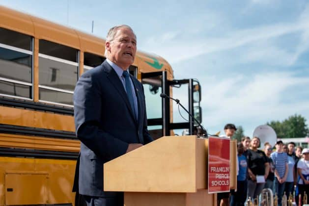 Speaker Gov. Inslee. stands in front of a new all-electric Blue Bird school bus.