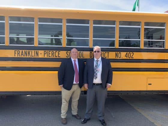Two district officials stand in front of a new all-electric Blue Bird school bus.