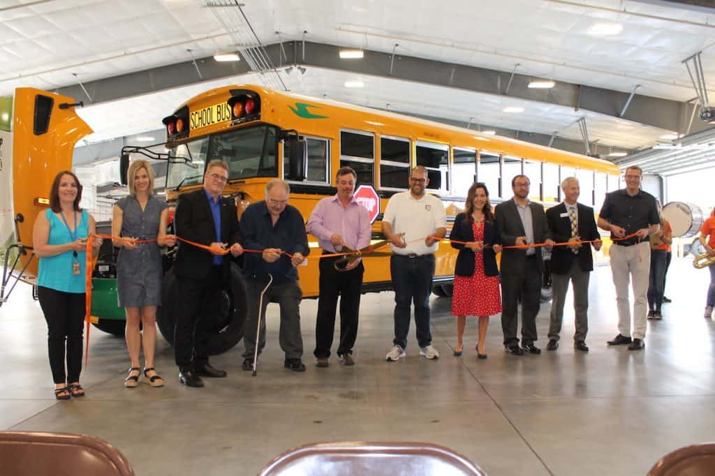 Ribbon cutting in front of a new e16 Blue Bird electric school bus