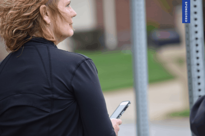 mother waiting at school bus stop with Here Comes The Bus app