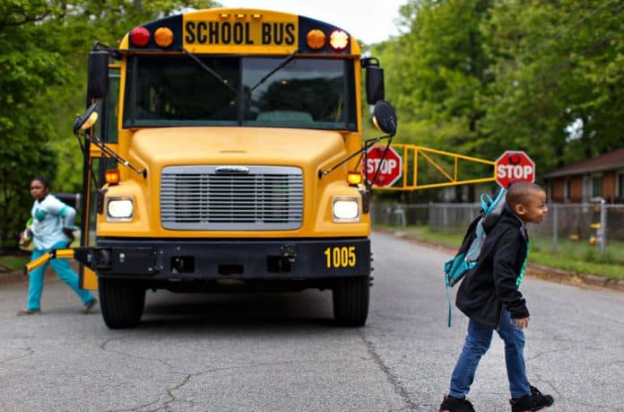 School bus using the extended stop arm with children present