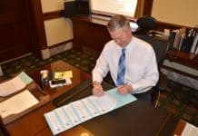 Gov. Little signing proclamations.