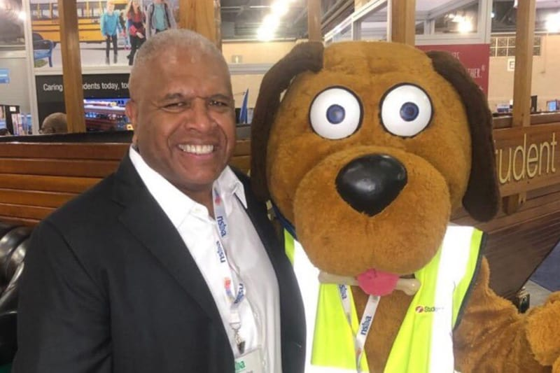 Dennis Maple with First Student mascot Safety Dog.