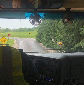 inside of school bus, looking over school bus driver's shoulder