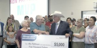 Ken Patterson received a check from Bob Funk at Express Employment of Oklahoma, in recognition of his 20 years of school bus driving. (Photo courtesy of Oklahoma's News 4.)