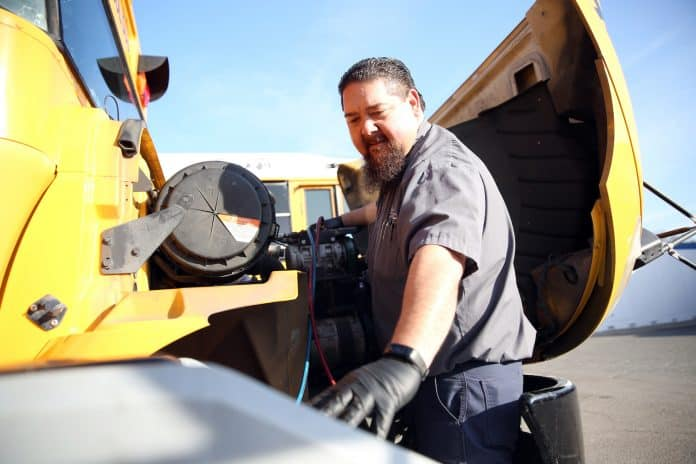 Ray Manolo works on a school bus. He discussed green bus maintenance at a summit on April 22, 2021. (Image courtesy of Twin Rivers Unified School District.)