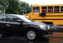 A car passes a school bus during a closed-road demonstration by Safe Fleet at the STN EXPO Indianapolis on June 9. 2019. Technology exists to both capture video of passing vehicles and alert students and bus drivers if other motorists are not stopping for the school bus. (Photo by Taylor Hannon.)
