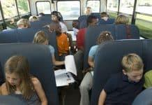 Students in school bus doing homework.