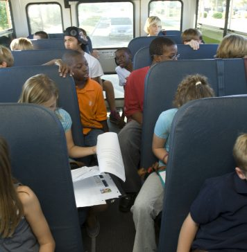 Students in school bus doing homework.
