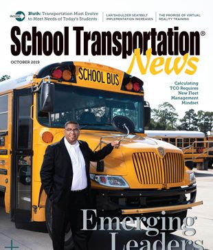 Ariel Rodriguez stands with an IC Bus.