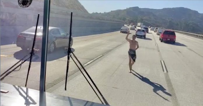 Screen capture of Fox 11 footage of an almost naked man running towards a school bus driving on I-5 in the Los Angeles-area this week.