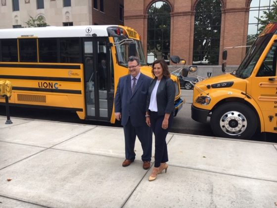 Michigan Gov. Gretchen Whitmer and Quebec Assistant Deputy Minister of International Affairs and La Francophonie Eric Marquis in front of the Lion Electric Co. electric bus (left) and the Thomas Built Buses / Proterra Saf-T-Liner C2 Jouley electric bus on Sept. 12, 2019.