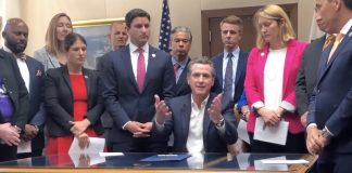Gov. Gavin Newsom (center) signed many bills into law on Oct. 13, including the controversial school start time bill. (Screen capture of video by the Sacramento Bee.)
