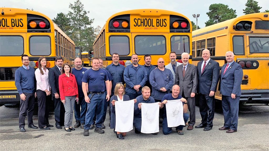 "EPA reps stand with district administrators and transportation personnel after the EPA conducted its ""white hanky"" test, exhibiting the difference in emissions from an old diesel bus (far right) with newer-model gas (far left) and propane vehicles."