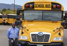 Greg Jackson, director of transportation and fleet services at Jefferson County Schools, poses with a Blue Bird school bus. (Photo by Taylor Hannon.)
