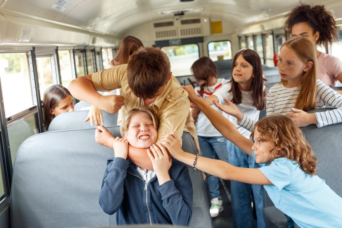 Stock photo of student bullying on a school bus.