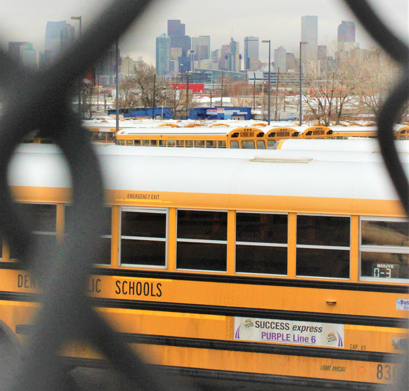 Denver Public Schools' purple Success Express parks at the Hilltop Terminal on Dec. 5, 2019, with the city skyline on the horizon.