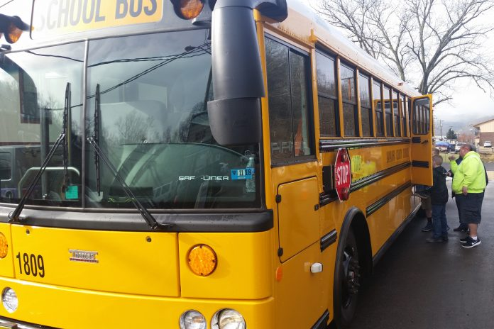Kanawha County Schools transportation staff in West Virginia practice school bus evacuation drills with students.