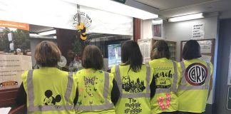 Transportation staff at Brewster Central School District pose with their newly decorate safety vests. The vests are improving department morale and encouraging conversations between transportation staff and the student riders.