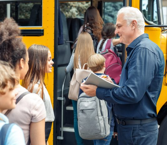 An older driver greets students as they board the school bus.