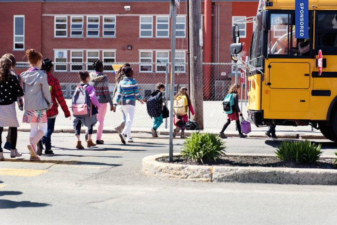 Multi-Ethnic Group of elementary school kids getting in a yellow school bus at school's out. Boys and girls age 6-11. They walk on behind another. They cross the street and the Stop sign of the yello school bus is open. This was taken in Quebec Canada.