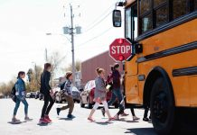 Group of elementary school kids getting in a yellow school bus.