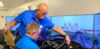 Larry Thorton, safety training specialist for Education Services Center Region 6 in Huntsville, Texas, shows a Klein ISD school bus driver how to operate the high-tech simulator. (Photo courtesy of Klein ISD)