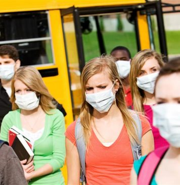 Students leaving a school bus in masks