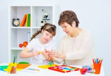 Girl with Down Syndrome works with her teacher at home
