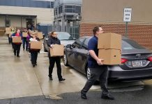 Gwinnett County Public Schools employees carry boxes of food to delivery points for students who are affected by coronavirus closures. (Photo courtesy of Gwinnett County Public Schools)