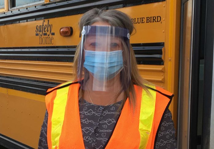 A school bus driver at Diversified Transportation BC wears a face mask and shield, as British Columbia students load and unload the bus. The driver can not where the shield when they are driving. (Photo courtesy of Donna Holmgren.)