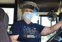 A Fullerton Unified School District bus driver in California, poses with with a face mask and shield.